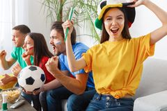 Group of friends sport fans watching match in colorful shirts girl screaming cheerful. Young women and men wearing colorful t-shirts watching tv soccer game Royalty Free Stock Photos