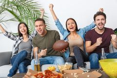Group of friends sport fans watching rugby match cheering team Stock Photos