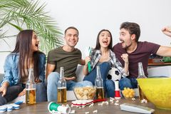 Group of friends sport fans watching soccer match hugging cheerful. Young women and men watching tv soccer match together hugging celebrating victory cheerful Stock Images