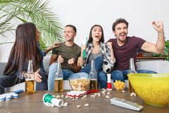 Group of friends sport fans watching soccer match screaming excited. Young women and men watching tv soccer match together hands up happy for team victory Royalty Free Stock Images