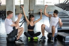 group of friends sport people celebrate and raising hands to success  after exercise in  gym . young fitness  in sportswear take a