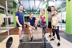 Group of friends with sports equipment in gym. Fitness, sport and healthy lifestyle concept - group of happy people with different sports equipment in gym stock photo