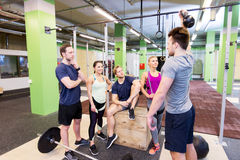 Group of friends with sports equipment in gym. Fitness, sport and healthy lifestyle concept - group of happy people with different sports equipment talking in Stock Images