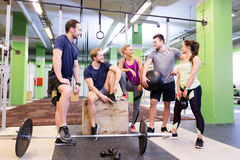 Group of friends with sports equipment in gym. Fitness, sport and healthy lifestyle concept - group of happy people with different sports equipment talking in Stock Photo