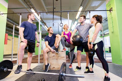 Group of friends with sports equipment in gym. Fitness, sport and healthy lifestyle concept - group of happy people with different sports equipment talking in royalty free stock image