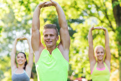 Group of friends or sportsmen exercising outdoors Stock Images