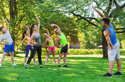 Group of friends or sportsmen exercising outdoors. Fitness, sport, friendship and healthy lifestyle concept - group of happy teenage friends or sportsmen Stock Photography