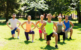 Group of friends or sportsmen exercising outdoors. Fitness, sport, friendship and healthy lifestyle concept - group of happy teenage friends or sportsmen Royalty Free Stock Photography