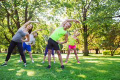 Group of friends or sportsmen exercising outdoors. Fitness, sport, friendship and healthy lifestyle concept - group of happy teenage friends or sportsmen Stock Photos