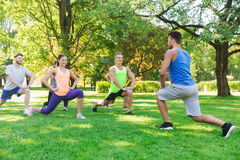 Group of friends or sportsmen exercising outdoors Royalty Free Stock Images