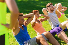 Group of friends or sportsmen exercising outdoors Royalty Free Stock Image