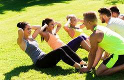 Group of friends or sportsmen exercising outdoors. Fitness, sport, friendship and healthy lifestyle concept - group of happy teenage friends or sportsmen Stock Images