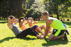 Group of friends or sportsmen exercising outdoors. Fitness, sport, friendship and healthy lifestyle concept - group of happy teenage friends or sportsmen Royalty Free Stock Photos