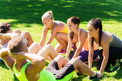 Group of friends or sportsmen exercising outdoors. Fitness, sport, friendship and healthy lifestyle concept - group of happy teenage friends or sportsmen Stock Photo