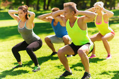 Group of friends or sportsmen exercising outdoors Stock Image