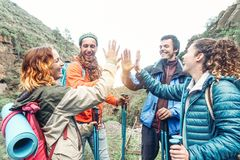 Group of friends stacking hands while doing trekking excursion on mountain - Young tourists walking and exploring the wild nature stock photos