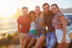 Group Of Friends Standing By Car On Coastal Road At Sunset Stock Photos