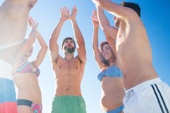 Group of friends standing in circle arms raised. At the beach Royalty Free Stock Photo