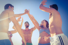 Group of friends standing in circle arms raised. At the beach Stock Image