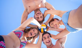 Group of friends standing in circle and holding ball. At the beach Stock Photography