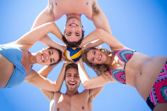 Group of friends standing in circle and holding ball. At the beach Stock Images