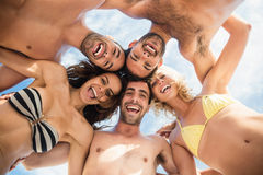Group of friends standing in circle and smiling at camera. On the beach Royalty Free Stock Photos