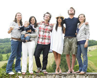 Group of Friends Standing Outdoors. Group of young people, with one woman holding a baby, standing on a stone wall outdoors. Horizontal royalty free stock images