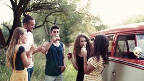 A group of friends standing outdoors on a roadtrip through countryside, clinking bottles. A group of young friends with drinks standing outdoors on a roadtrip stock video footage