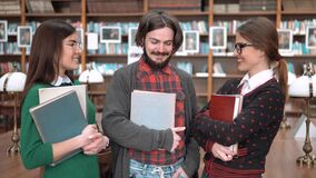 Group of Friends Students. Happy students having lovely talk in library, two young women and bearded man chatting in front of bookshelves, holding books and stock video footage