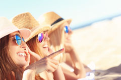 Group of friends sunbathing on the beach Stock Photo