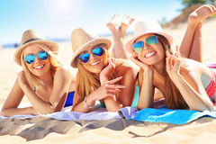 Group of friends sunbathing on the beach Stock Images