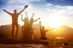 Group friends sunrise mountains happy. Group of happy friends sits with raised hands on background of sunset or sunrise bay with islands. Space for text Stock Photos