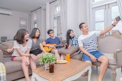 Group of friends take picture with smartphone and sing song with. Guitar at home. Concept about friendship, home entertainment and people stock photos