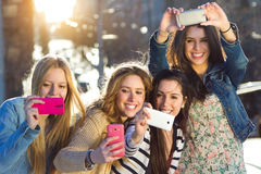 A group of friends taking photos with a smartphone Stock Photos