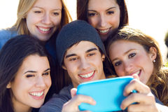 A group of friends taking photos with a smartphone Stock Photo