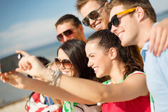 Group of friends taking picture with smartphone Royalty Free Stock Image