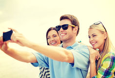 Group of friends taking picture with smartphone stock photography