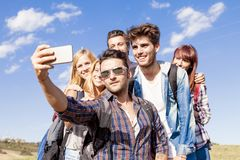 Group of friends taking a self portrait. Group of smiling friends taking a self portrait outdoor in the mountain Stock Photography