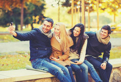 Group of friends taking selfie in autumn park Stock Images