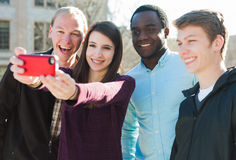 Group of Friends Taking a Selfie. Group of diverse friends taking a selfie outside Stock Photo