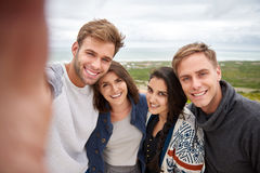 Group of friends taking a selfie outdoors in nature. Smiling friends taking a group selfie while on a nature hike outdoors stock image