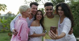 Group Of Friends Taking Selfie Photo On Cell Smart Phone On Summer Terrace Over Sunset Landscape, Friends Posing For stock video footage