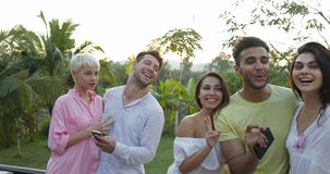 Group Of Friends Taking Selfie Photo On Cell Smart Phone On Summer Terrace Over Sunset Landscape, Friends Posing For stock footage