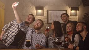 The group of friends are taking selfies and making funny faces, drinking beer at the background of the football pub. The. Close-up portrait stock footage