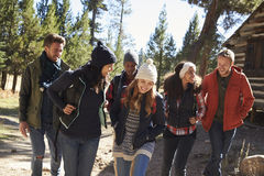 Group of friends talk as they hike past a cabin in a forest Royalty Free Stock Photos
