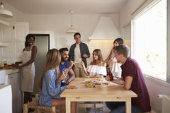 Group of friends talk in kitchen, one preparing food Stock Photography