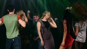 Group of friends talking while dancing to the. Music. Action takes place in a nightclub.  In the foreground two women dancing. One of which is a red dress. Slow stock video
