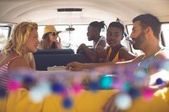 Group of friends talking with each other in a camper van at beach. Front view of happy group of diverse friends talking with each other in a camper van at beach stock photo
