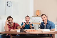 Group of friends with tasty food laughing while watching TV stock photos