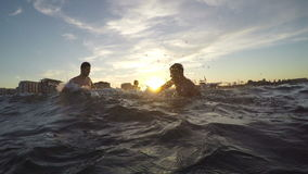 Group of friends teasing one another and playing with water in the sea on sumertime stock video footage